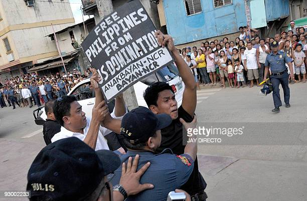A protestor clashes with police as US Secretary of State Hillary Clinton visits the typhoon affected Malanday High School in Marikina suburban Manila...