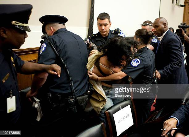 Protestor Diane Wilson is removed by Capitol Hill police officers as Tony Hayward chief executive officer of BP Plc testifies to a House Energy and...