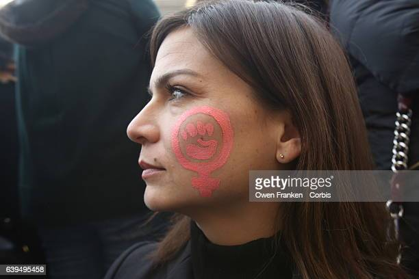 A protestor displays a feminist symbol painted on her cheek as over 2000 people protest during the Women's march on the Trocadero in front of the...