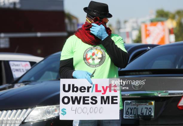 Protestor displays a sign as Uber and Lyft drivers with Rideshare Drivers United and the Transport Workers Union of America prepare to conduct a...