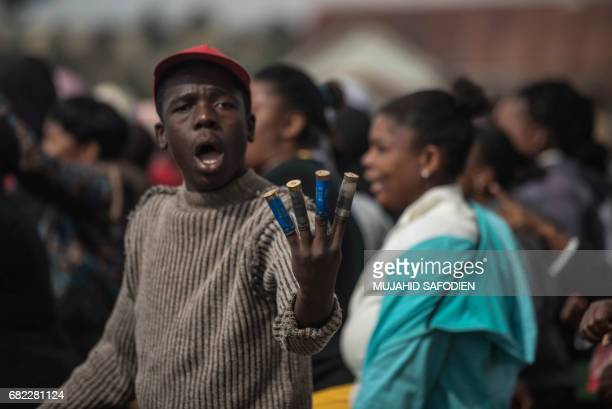 A protestor displays empty rubber bullet casings on his fingers as residents from Matole township in Roodepoort gather waiting for government...