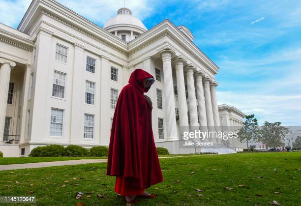 A protestor dressed as a character from the Hulu TV show The Handmaid's Tale based on the bestselling novel by Margaret Atwood walks back to her car...