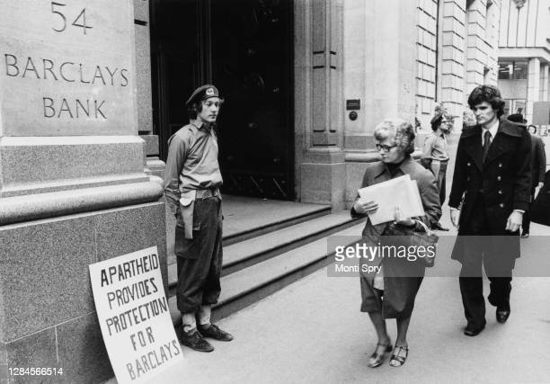 Protestor dressed as a 'South African Military Guard' beside a placard reading 'Apartheid provides protection for Barclays', standing guard outside...