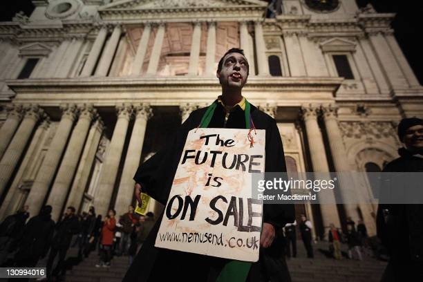 A protestor dressed as a Zombie carries a placard in front of St Paul's Cathedral on October 31 2011 in London England The Dean of St Pauls Cathedral...