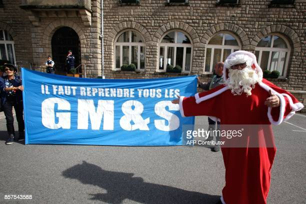 A protestor dressed as Santa Claus to emphesize a quote in June by the French president in which he said he said he would try his best but he was...