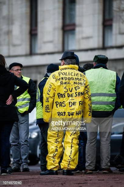 A protestor dressed in a yellow overall stands near the Chateau de Versailles in Versailles outside Paris ahead of a 'Yellow Vest' demonstration on...