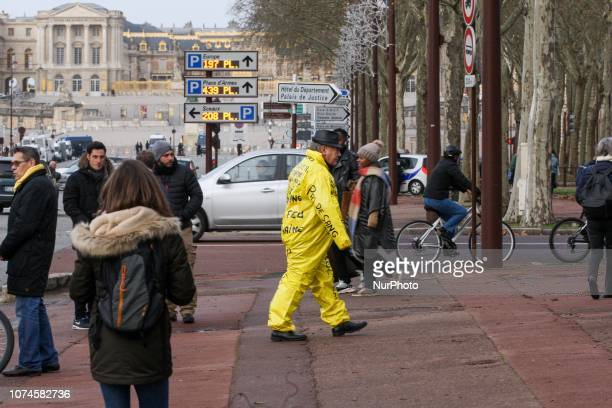 A protestor dressed in a yellow overall stands near the Chateau de Versailles in Versailles outside Paris ahead of a quotYellow Vestquot...