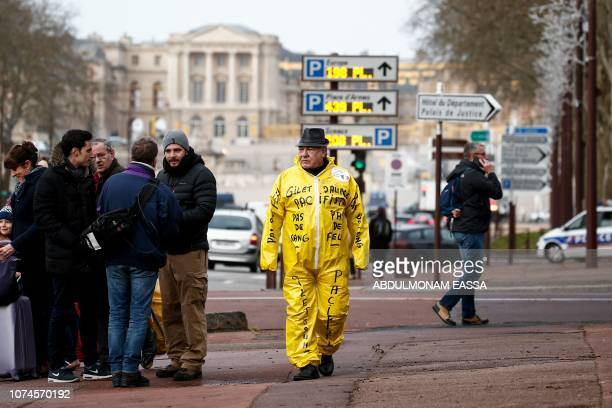 A protestor dressed in a yellow overall walks near the Chateau de Versailles in Versailles outside Paris ahead of a 'Yellow Vest' demonstration on...