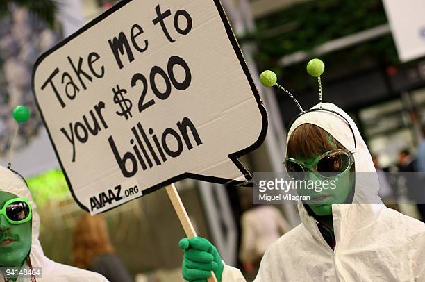 A protestor dressed like an alien holds a banner reading 'Take me to your 200 billion dollars' during the second day of the United Nations Climate...