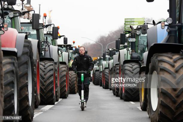 A protestor drives on an escooter along lined up tractors during a protest on November 26 2019 in Berlin against the German government's agricultural...