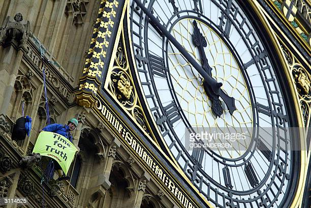 A protestor from Greenpeace sits on the face of London's landmark Big Ben clock tower with a banner that reads 'Time for Truth' 20 March 2004 as...