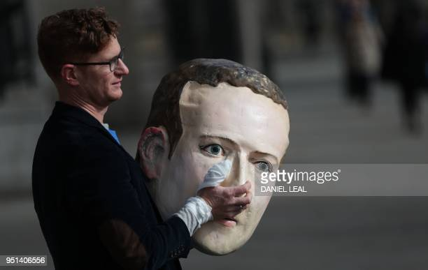 A protestor from the pressure group Avaaz carries a papier mache head of Facebook founder Mark Zuckerberg outside Portcullis house where Facebook's...