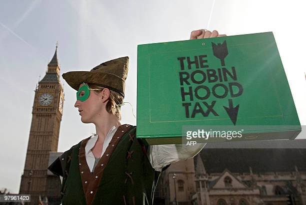 A protestor from the 'Robin Hood Tax Campaign' dressed as 'Robin Hood' holds a fake budget box above the Houses of Parliament in London on March 23...