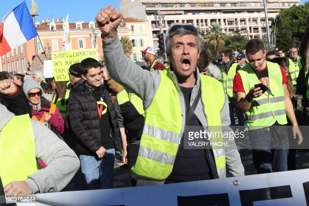 A protestor gestures on the 'Promenade des Anglais' during a protest of Yellow vests against rising oil prices and living costs in Nice southeastern...