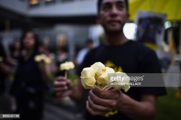 A protestor gives away miniature paper yellow umbrellas during a gathering outside the government headquarters to mark the third anniversary of mass...