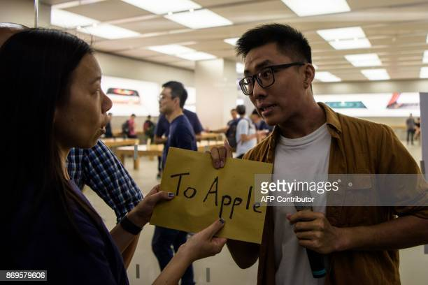 A protestor hands a letter to an Apple store representative on the release date of their 10th anniversary iPhone X in Hong Kong on November 3 2017 /...
