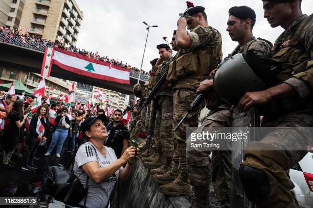 A protestor hands roses to soldiers who had earlier tried to force demonstrators to clear the highway leading out of Beirut on October 23 2019 in Jal...