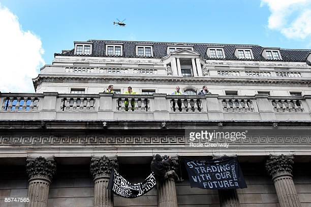 A protestor hangs a banner from the Bank of England building during G20 demonstrations in the City of London on April 1 2009 in London England...