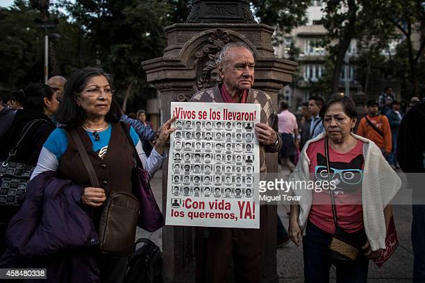 Protestor hold a sign reading the slogan 'Alive they took them alive we want them back' on Reforma Avenue during a demonstration to ask for justice...