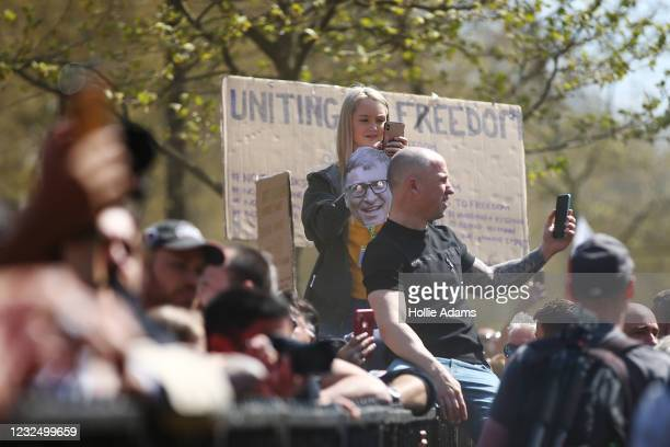 """Protestor holding a Bill Gates mask takes a photo of other protestors during a """"Unite For Freedom"""" anti-lockdown demonstration held to protest..."""