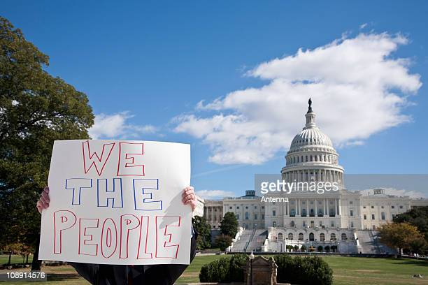 a protestor holding a placard in front of the us capitol building - 抗議者 ストックフォトと画像