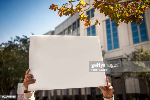 protestor holding up blank sign - demonstrant stock-fotos und bilder