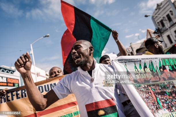 A protestor holds a banner in front of a Biafra flag as he takes part in a demonstration in Durban South Africa on May 30 2019 during a Freedom March...