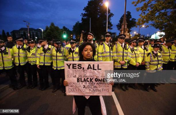 A protestor holds a banner in front of police personnel in Brixton south London during a demonstration against police brutality in the US on July 9...