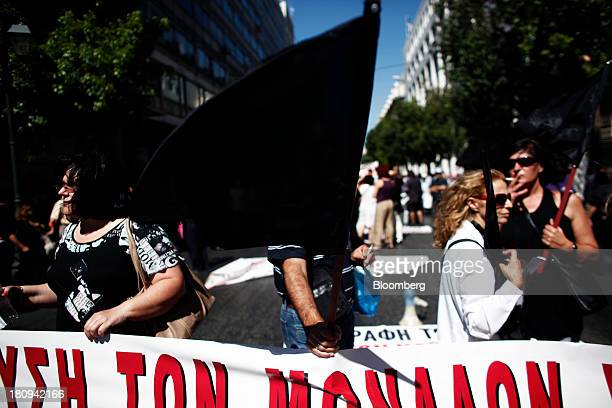 A protestor holds a black flag during a demonstration to mark the start of a 48hour strike by Greece's biggest publicsector union ADEDY in central...