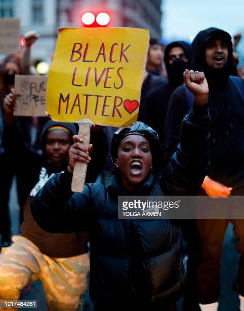 "Protestor holds a ""Black Lives Matter"" placards as she demonstrates in Parliament Square, during an anti-racism demonstration in London, on June 3..."