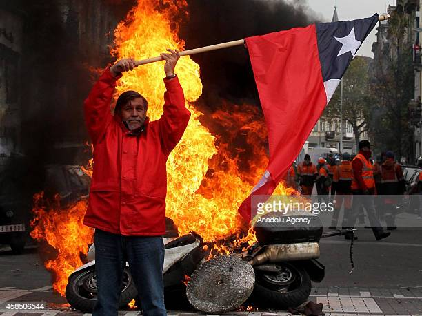 A protestor holds a Chile flag in front of burning police motorbike in Brussels on November 6 2014 Belgians protest government's policies that will...