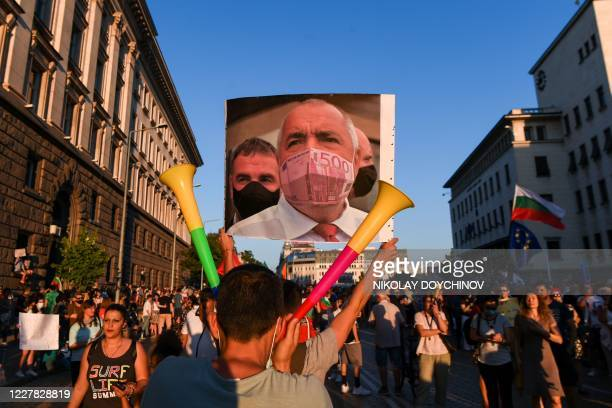 Protestor holds a collage mocking the Bulgarian Prime minister wearing a protective mask made of a 500 euros bill during an anti-government protest...