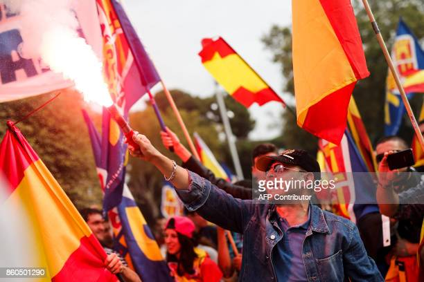 A protestor holds a flare during an ultraright wing antiseparatist demonstration for the unity of Spain called by 'Falange Espanola' during the...