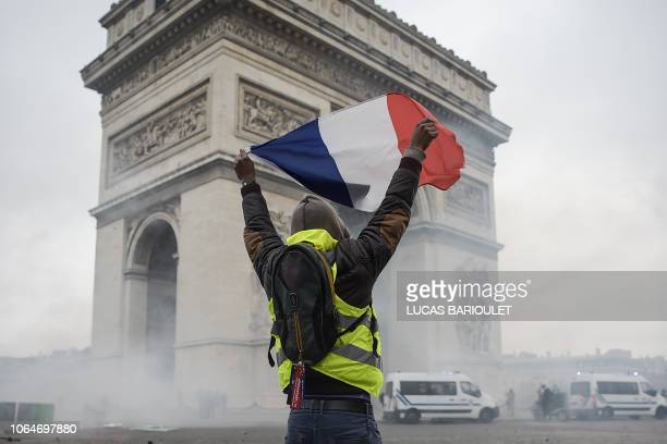 TOPSHOT A protestor holds a french flag amid tear gas in front of the Arc de Triomphe near the Champs Elysees in Paris on November 24 2018 during a...
