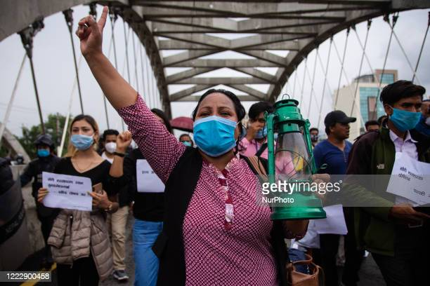 Protestor holds a lantern in a protest against killing of Dalit low-caste youth in Rukum district during lockdown in Kathmandu, Nepal on Thursday,...