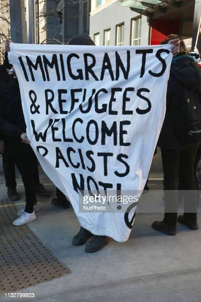 Protestor holds a large banner saying 'Immigrants and refugees welcome racists not' during a ProMuslim and AntiMuslim rally held in Toronto Ontario...