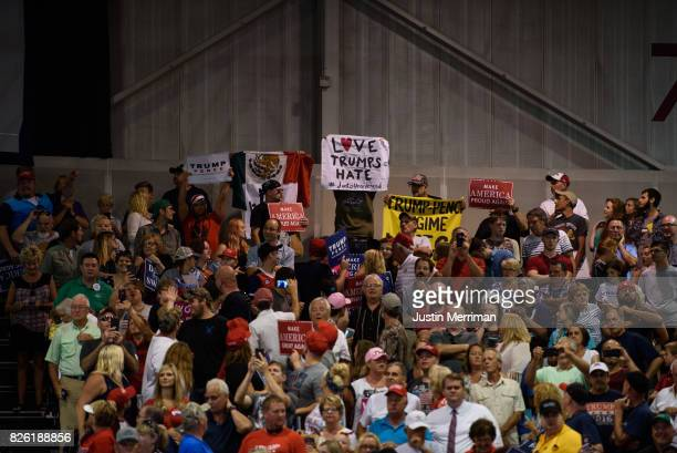 A protestor holds a 'Love Trumps Hate' banner at President Donald J Trump's campaign rally at the Big Sandy Superstore Arena on August 3 2017 in...