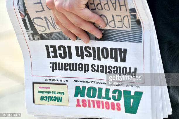 Protestor holds a newspaper published by Socialist Action ahead of an Abolish ICE protest to demand the halt of deportations and an end to family...