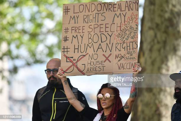 Protestor holds a placard as a small group of anti-lockdown protesters gather outside New Scotland Yard in Victoria, London on May 2 during the...