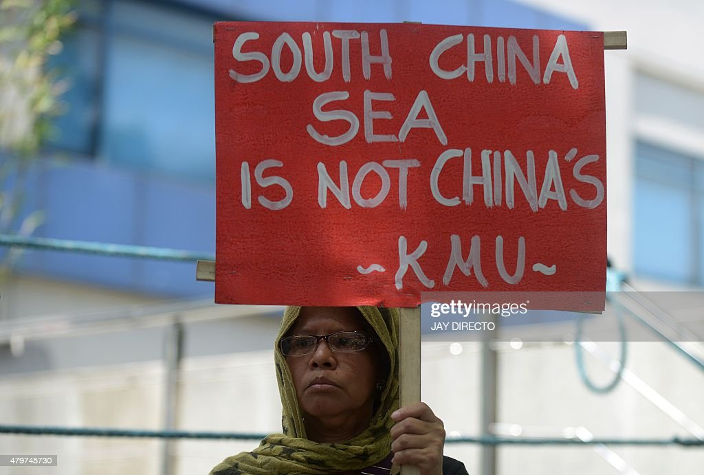 A protestor holds a placard at a rally in front of the Chinese Consulate in Manila's financial district on July 7, 2015, denouncing China's claim to most of the South China Sea including areas claimed by the Philippines. The protest comes as a UN tribunal in the Hague begins a hearing on a Philippine suit challenging China's claim over disputed islands in the South China Sea. The Philippines has become increasingly vocal in criticising China's aggressiveness in staking its claim, including the building of artificial islands using reclaimed land in the disputed waters. AFP PHOTO / Jay DIRECTO