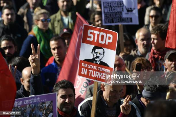 TOPSHOT A protestor holds a placard depicting a caricature of Turkish President reminding Germany's late dictator Adolf Hitler during a demonstration...