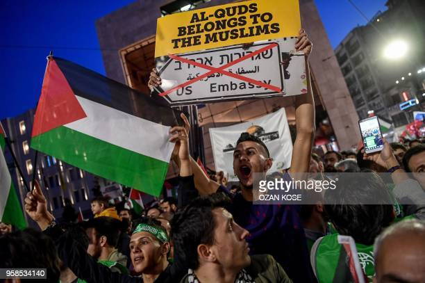 TOPSHOT A protestor holds a placard reading 'AlQuds belongs to the muslims' as he shouts slogans among people holding Palestinian flags while they...