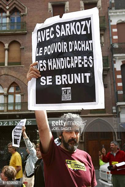 """Protestor holds a placard reading """"With Sarkozy, buying power of disabled people gets dark"""" to ask for more buying power, on July 13 2008 in..."""