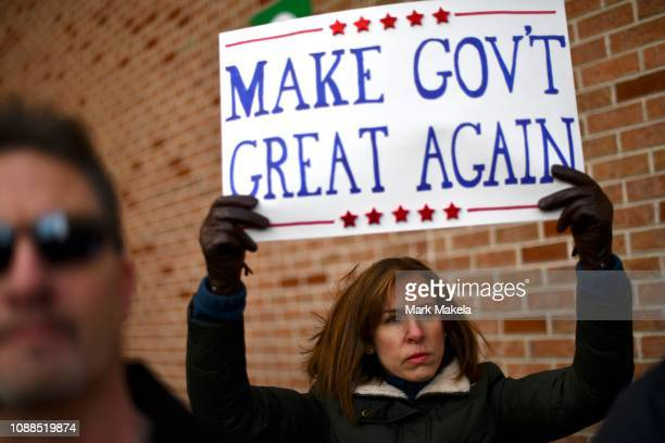 A protestor holds a placard stating MAKE GOV'T GREAT AGAIN while demonstrating with Philadelphia Airport TSA and airport workers outside the...