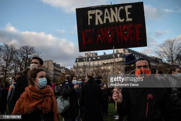 Protestor holds a placard that reads 'France Islamophobe' during a demonstration against the French government's global security bill and...