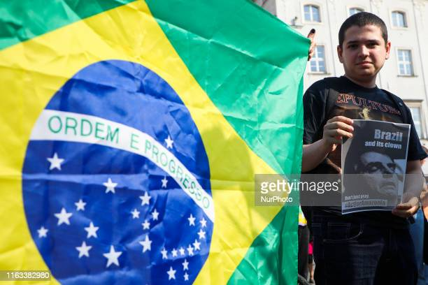 A protestor holds a poster with the picture of Brazilian President Jair Bolsonaro during 'SOS Amazonia' protest organized by the Youth Climate Strike...
