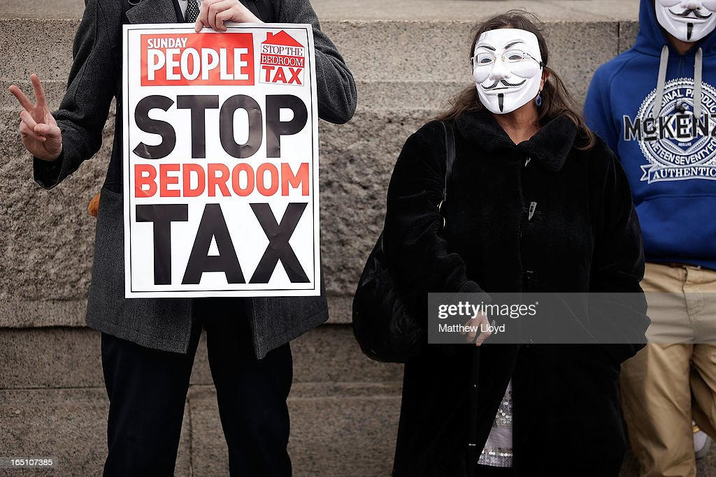 A protestor holds a sign as he makes the peace sign as others wear masks while demonstrating against the proposed 'bedroom tax' gather in Trafalgar Square before marching to Downing Street on March 30, 2013 in London, England. Welfare groups are protesting the government's plans to cut benefits where families have surpassed the number of rooms they require.