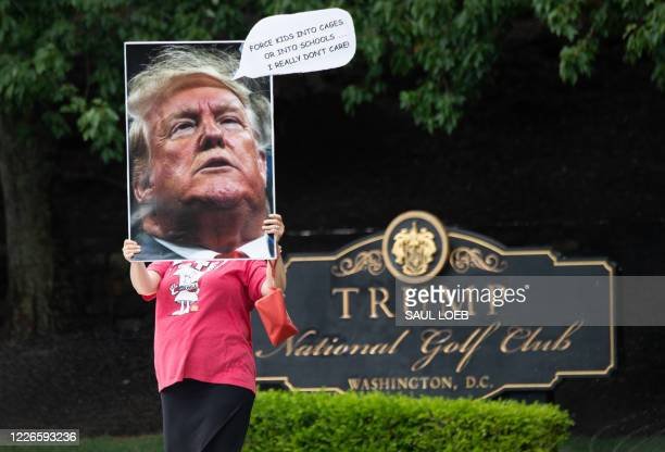 Protestor holds a sign as US President Donald Trump visits Trump National Golf Club in Sterling, Virginia, July 12, 2020.