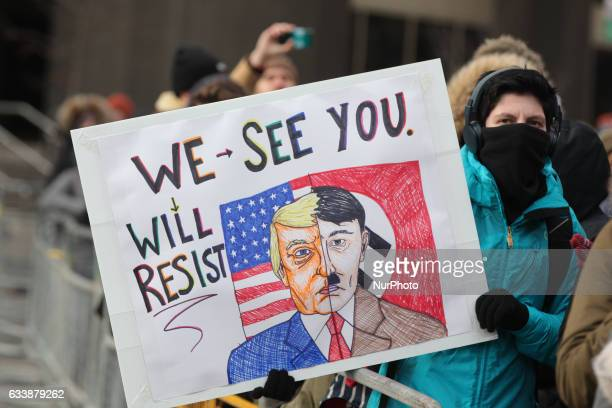 Protestor holds a sign comparing President Donald Trump to Adolf Hitler as thousands of Canadians take part in a massive protest against President...