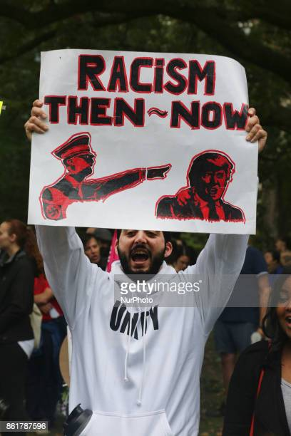 Protestor holds a sign comparing US President Donald Trump to Hitler during in a rally against White Supremacy and Islamophobia at Queen's Park in...